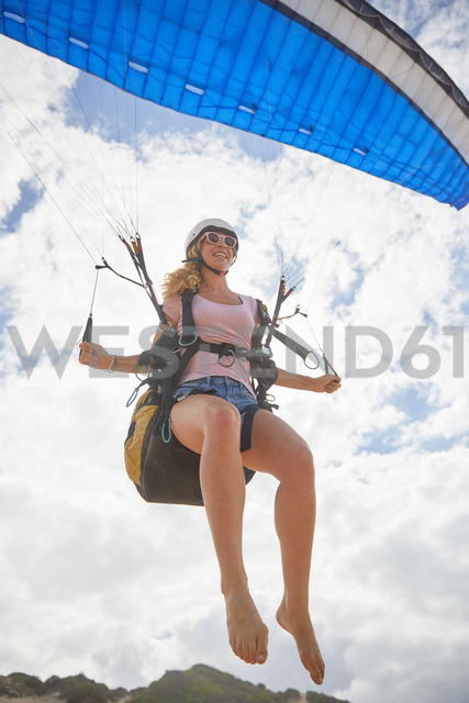 Smiling female paraglider mid-air - CAIF21721