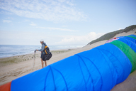 Male paraglider with parachute on ocean beach - CAIF21724