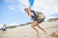 Female paraglider running, taking off on beach - CAIF21727