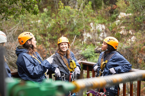 Smiling women friends talking, waiting to zip line - CAIF21736