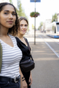 Two young women crossing street in the city - HHLMF00307