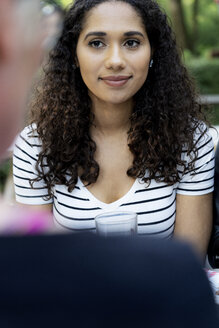Portrait of a young woman sitting in beer garden, looking at a friend - HHLMF00322
