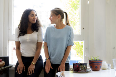 Two female friends sitting at home at the window - HHLMF00337