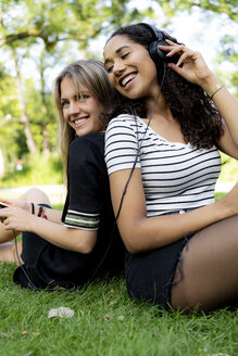 Two girlfriends in a park listening music, using smartphone - HHLMF00352