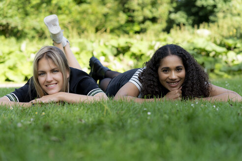 Two girlfriends relaxing in grass in a park - HHLMF00355