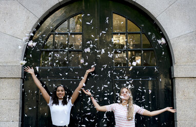 Two happy girlfriends throwing petals - HHLMF00364