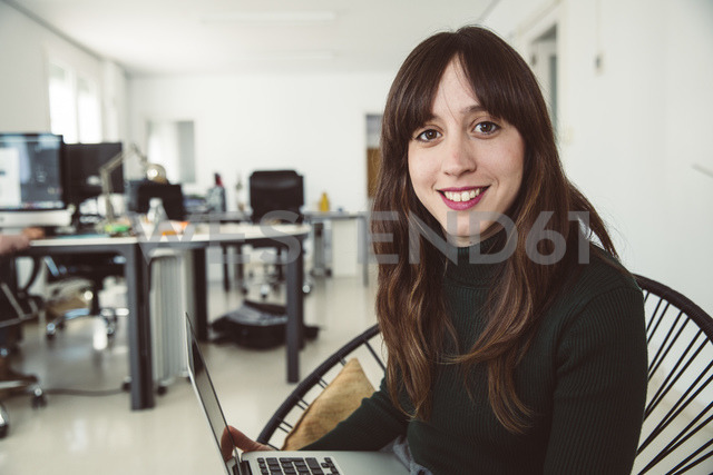Young businesswoman sitting in her office, smiling - SUF00539 - Sullivan/Westend61