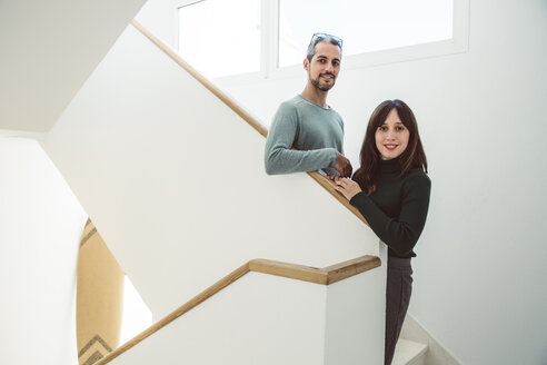 Business couple standing on stairs of their office - SUF00542