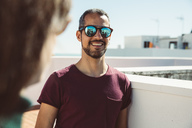 Portrait of a man, talking to woman on a roof, enjoying summer - SUF00545