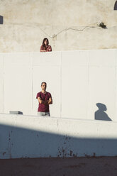 Man and woman standing on different levels of a wall, with arms crossed - SUF00557