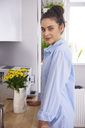 Young woman at home, standing in kitchen - ABIF00894