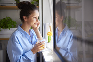 Young woman drinking orange juice in her kitchen - ABIF00897