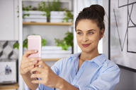 Young woman at home in kitchen, taking selfie - ABIF00903