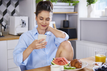 Young woman at home in kitchen, using smartphone - ABIF00909
