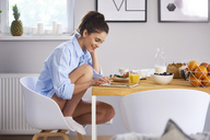 Young woman at home in kitchen, eatinng breakfast, using digital tablet - ABIF00912