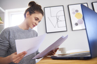 Young woman working from home, using laptop, reading papers - ABIF00915