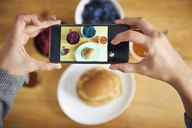 Young woman taking pictures of breakfast pancakes with berries and fresh fruit - ABIF00927