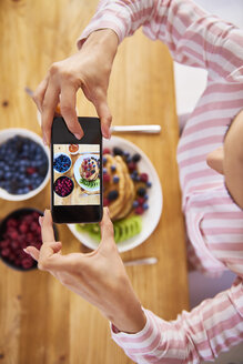 Young woman taking pictures of breakfast pancakes with berries and fresh fruit - ABIF00933