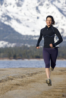 Woman running on beach in winter conditions in Lake Tahoe, California. - AURF01537