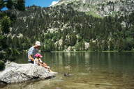 Spain, Father and daughter sitting on a rock at a mountain lake, feeding ducks - GEMF02347