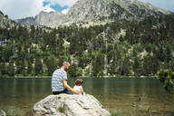 Spain, Father and daughter sitting on a rock at a mountain lake, feeding ducks - GEMF02350