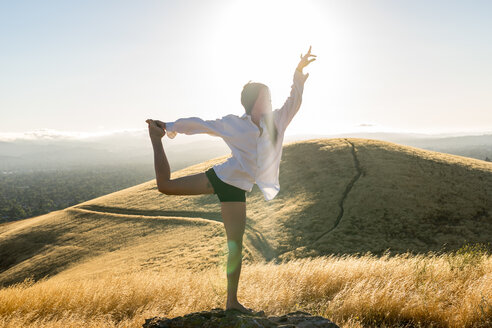 Woman in yoga pose in a field of golden grass in sun drenched hills of California. - AURF01653