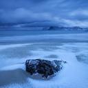 Waves wash over snow covered sand in winter at Storsandnes beach, Flakstad├©y, Lofoten Islands, Norway - AURF01689