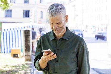 Smiling mature man using cell phone in the city - TCF05697