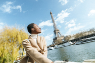 France, Paris, Woman with closed eyes at river Seine with the Eiffel Tower in the background - KIJF02002
