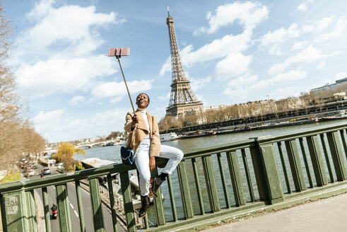 France, Paris, Woman sitting on bridge over the river Seine with the Eiffel tower in the background taking a selfie - KIJF02005