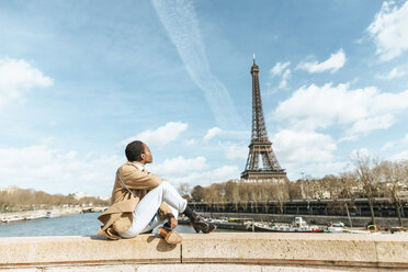 France, Paris, Woman sitting on bridge over the river Seine looking at Eiffel tower - KIJF02008
