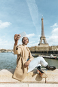 France, Paris, Woman sitting on bridge over the river Seine with the Eiffel tower in the background taking a selfie - KIJF02011