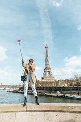 France, Paris, Woman standing on bridge over the river Seine with the Eiffel tower in the background taking a selfie - KIJF02014