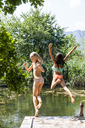 Two carefree girls jumping into pond - TCF05719