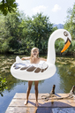 Happy girl standing on jetty at a pond with inflatable pool toy in swan shape - TCF05722