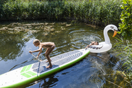 Two girls in a pond with inflatable pool toy in swan shape and SUP board - TCF05728