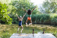 Two carefree girls jumping into pond - TCF05734