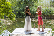Two girls standing face to face on jetty at a pond in fancy dresses - TCF05743