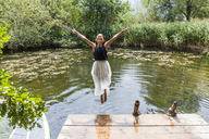 Carefree girl jumping into pond - TCF05746