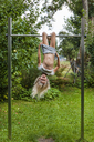 Carefree girl exercising on gymnastics bar in garden - TCF05749