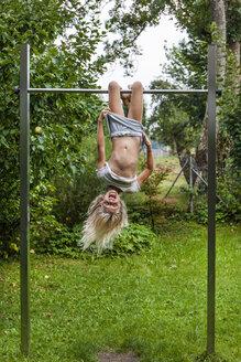 Carefree girl exercising on gymnastics bar in garden - TCF05749