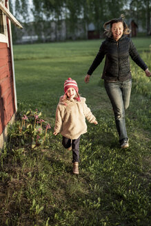 Finland, Kuopio, mother with daughter running at a cottage in the countryside - PSIF00029