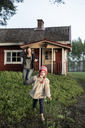Finland, Kuopio, mother with daughter running at a cottage in the countryside - PSIF00035