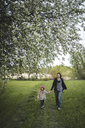 Finland, Kuopio, mother walking with daughter on a rural meadow - PSIF00038