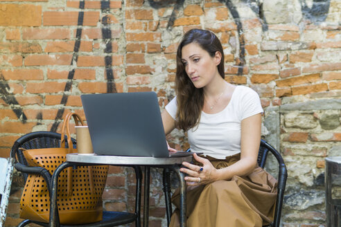 Woman using laptop at an outdoor cafe - FBAF00003