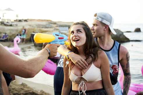 Crete, Chersonisou, Beach Party, woman getting tequila shot with water gun, man embracing her from behind - BEF00181