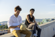 Two young men sitting and talking on a wall - AFVF01482