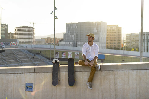 Young man sitting on urban wall next to skateboards at sunset - AFVF01488