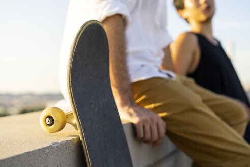 Close-up of two young men with skateboards sitting on a wall - AFVF01491