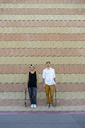 Two smiling young men with skateboards standing at a wall - AFVF01494